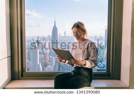 Smiling female office coworker working on modern tablet computer while sitting on window sill with panoramic views on New York city. Hipster girl browsing social network on touch pad, online banking #1341390080