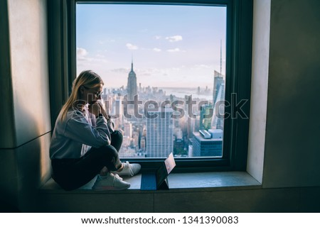 Pensive female office employee thinking on creating new project while sitting on window sill with scenery view of New York downtown. Hipster girl digital nomad working on modern tablet during travel #1341390083