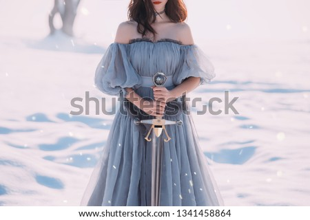 warlike girl brunette hair long blue vintage dress beautiful young lady. winter nature snow. sharp silver sword in hands goddess of death character computer game. mysterious woman silhouette red lips #1341458864