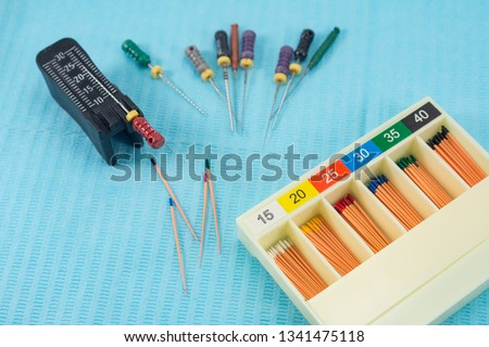 gutta-percha pins in a set of different sizes for root canal filling, endodontic ruler close-up, material for endodontic filling #1341475118