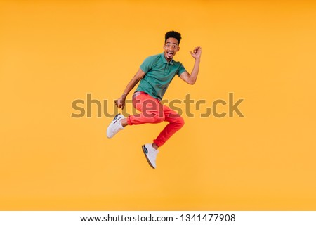 Joyful short-haired guy jumping on yellow background. Indoor photo of stunning male model in green t-shirt having fun in studio. #1341477908