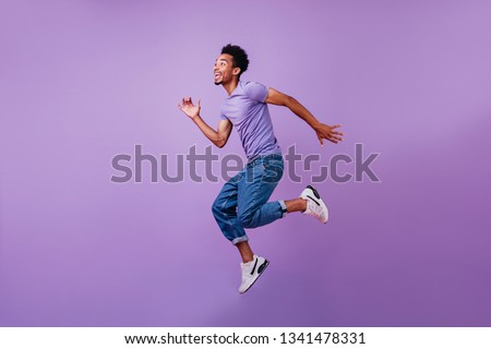 Portrait of jumping amazed guy in white sneakers. Indoor shot of dancing stylish male model in purple t-shirt. #1341478331
