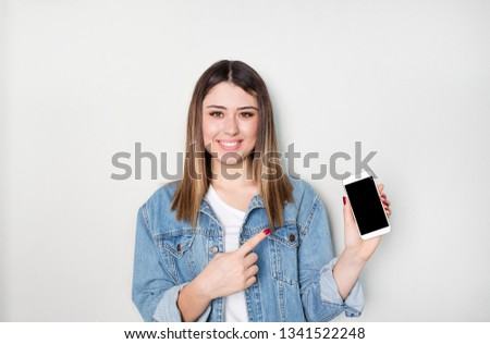 Smiling woman is pointing on smartphone standing on white background. #1341522248