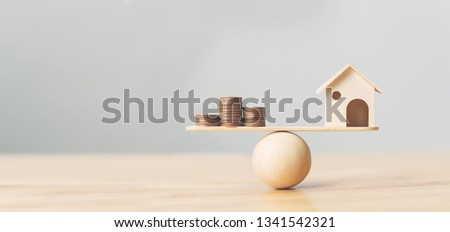 Wooden home and money coins stack on wood scale. Property investment and house mortgage financial real estate concept #1341542321