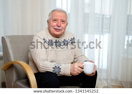 Portrait of Happy and smiling senior male 70-75 years old sitting on the armchair and holding cup of coffee in hand on window background #1341545252