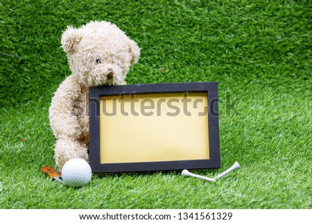 Bear golfer with blank board and golf ball on green grass
