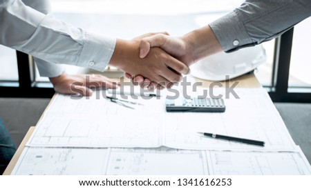Handshake of collaboration, Construction engineering or architect discuss a blueprint and building model while checking information on sketching, meeting for architectural project of partner. #1341616253