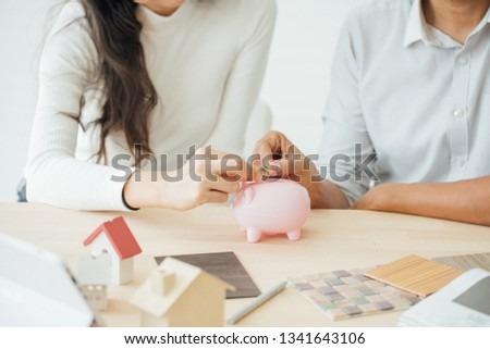 Businessman putting a coin into a pink piggy bank concept for savings and finance.Couple dreaming of new home. #1341643106
