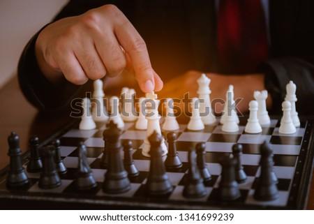 ฺีBusiness mans play chess board game. A white chess team and black chess team  idea for business competition and team work in business concept. #1341699239