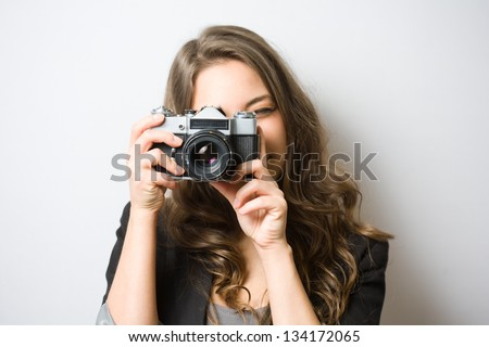 Portrait of fashionable young photographer with vintage film camera.