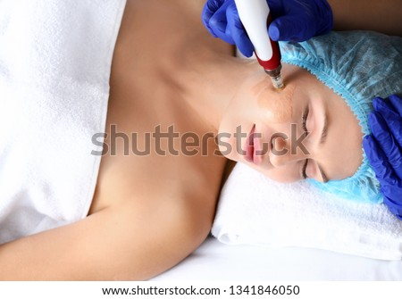 Young woman undergoing procedure of bb glow treatment in beauty salon Royalty-Free Stock Photo #1341846050