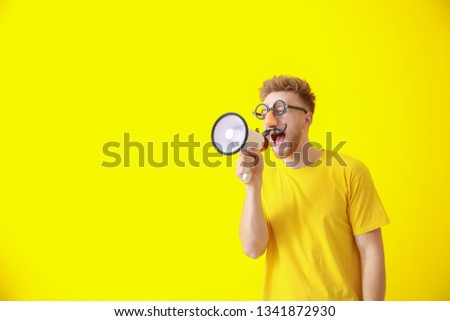 Funny man with megaphone on color background. April Fools' Day prank #1341872930