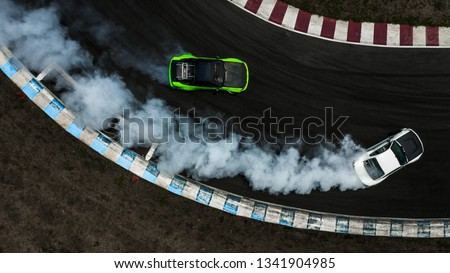 Two cars drifting battle on race track with smoke, Aerial view two car drifting battle. #1341904985