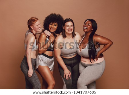 Smiling group of women in different size standing together in sportswear against brown background. Diverse group women looking at camera and laughing. #1341907685