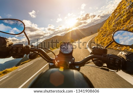 Motorcycle driver riding in Alpine highway, handlebars view, Austria, central Europe. #1341908606