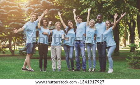 Happy millennial volunteers greeting you, waving hands and cuddling together at park, free space #1341917927