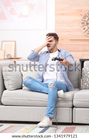 Emotional young man playing video games at home #1341979121