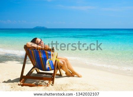 Woman enjoying vacation holidays on the beach and relaxing in a wooden chair near the sea in warm sunny summer day on island Phi Phi, Thailand Travel background  #1342032107