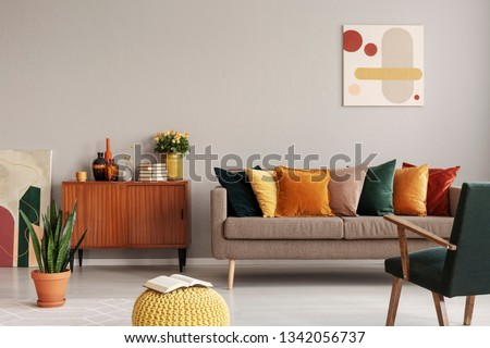 Abstract painting on grey wall of retro living room interior with beige sofa with pillows, vintage dark green armchair and yellow pouf with book #1342056737