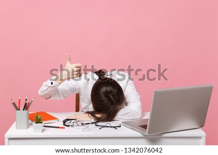 Female doctor laid her head down on desk, work on computer, medical document in hospital isolated on pastel pink background. Woman in medical gown glasses stethoscope. Healthcare medicine concept #1342076042