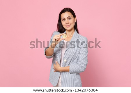 Portrait of smiling young woman in striped jacket holding bitcoin, future currency isolated on pink pastel wall background in studio. People sincere emotions, lifestyle concept. Mock up copy space #1342076384