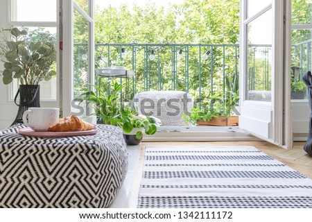 Pouf with pink plate with coffee mug and croissant in blurred foreground in real photo of room with fresh plants, rug on the floor and open door to balcony #1342111172