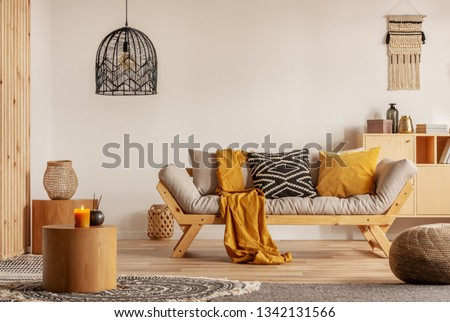 Scandinavian sofa with pillows and dark yellow blanket in bright living room interior with black chandelier #1342131566