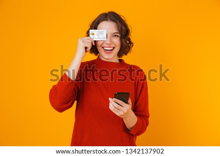 Portrait of positive woman 20s wearing sweater using cell phone and credit card while standing isolated over yellow background #1342137902
