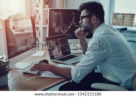 Developing new approaches. Thoughtful young businessman in formalwear analyzing data using computer while sitting in the office Royalty-Free Stock Photo #1342151180