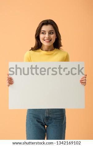 Blissful smiling brunette girl holding blank placard isolated on orange #1342169102