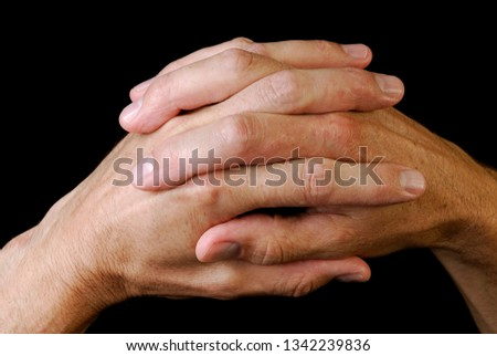 Close up of clasped hands on a black background #1342239836
