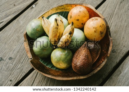 Organic tropical fruits in a platter: snake fruit, passion fruit, bananas. Assorted exotic fruit plate located on a wooden rustic background. Top view. Vegan detox healthy concept. Selective focus.  #1342240142
