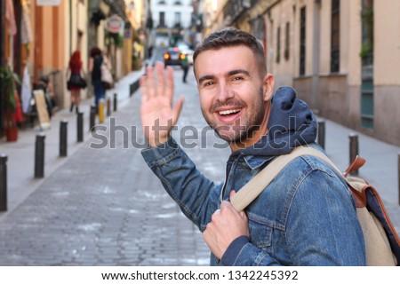 Cute guy saying hi outdoors  #1342245392