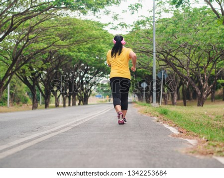 Overweight woman running in the park. Weight loss concept #1342253684