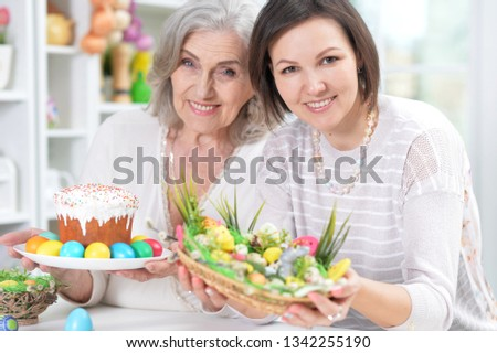 Close-up portrait of mother and daughter colouring eggs #1342255190