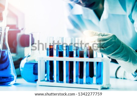 Woman scientist working in laboratory and examining biochemistry sample in test tube. Science technology research and development study concept. #1342277759
