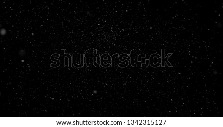 Flying dust particles on a black background Royalty-Free Stock Photo #1342315127