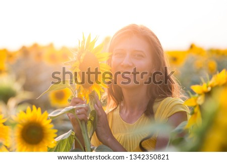 Beautiful woman with long hair in white dress in a field of sunflowers in the summer in the sunlight #1342350821