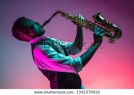 African American handsome jazz musician playing the saxophone in the studio on a neon background. Music concept. Young joyful attractive guy improvising. Close-up retro portrait. #1342370426