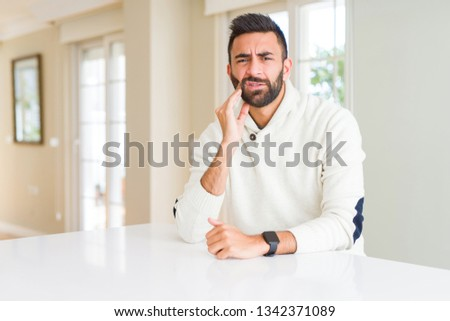 Handsome hispanic man wearing casual white sweater at home touching mouth with hand with painful expression because of toothache or dental illness on teeth. Dentist concept. #1342371089