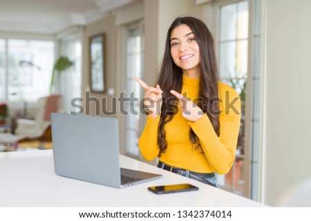 Young woman using computer laptop smiling and looking at the camera pointing with two hands and fingers to the side. #1342374014
