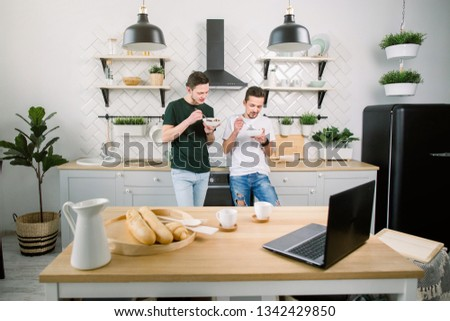 Happy homosexual boys talking each other and having breakfast. Everyday morning routine of gay couple life in kitchen at home #1342429850