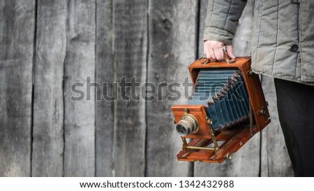 Large format retro camera in photographer hand. Concept - photography of the 1930s-1950s. Retro wooden wall on background, copy space for text