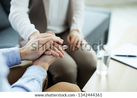 Hand of young woman between those of counselor supporting her during psychological session #1342444361
