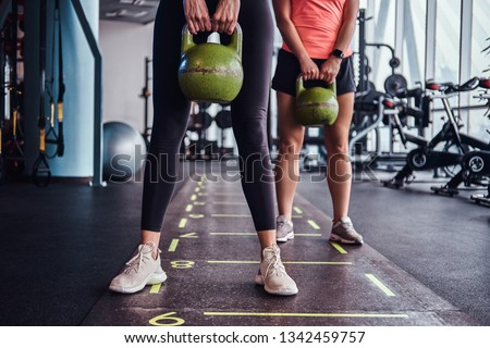 Two sportive girls trains with kettlebells in the modern gym. Health, diet, sport. #1342459757