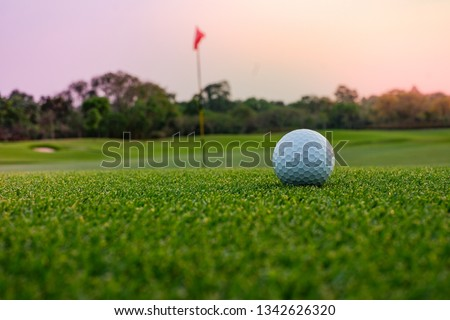 A long putt on the  green as sunset closes in Royalty-Free Stock Photo #1342626320