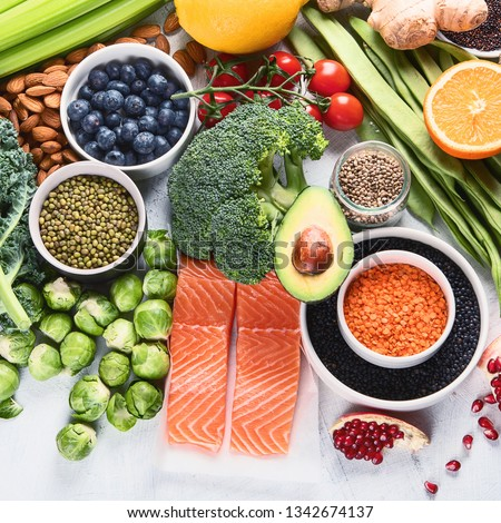 Selection of healthy food. Clean eating concept. Cooking ingredients with fish, superfood, vegetables,  artichokes, brussel sprouts, fruits, legumes  and blueberries #1342674137