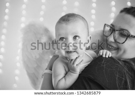 boy with his mouth open is lying on a white background with wings behind his back. Angel Cupid looks up #1342685879