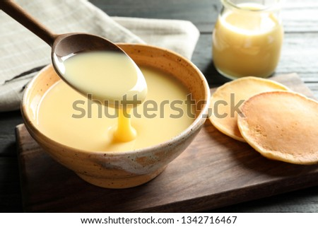 Spoon of pouring condensed milk over bowl on table, space for text. Dairy products Royalty-Free Stock Photo #1342716467