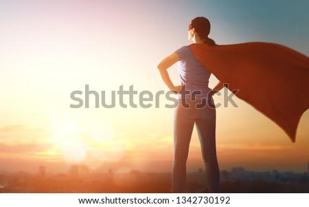 Joyful beautiful young woman in superhero costume posing on sunset background.